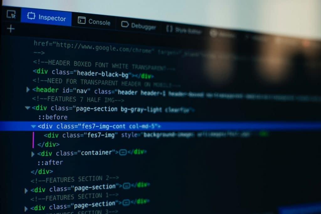 Ilustracją jest zdjęcie monitora, które na czarnym tle prezentuje fragmenty kodu HTML