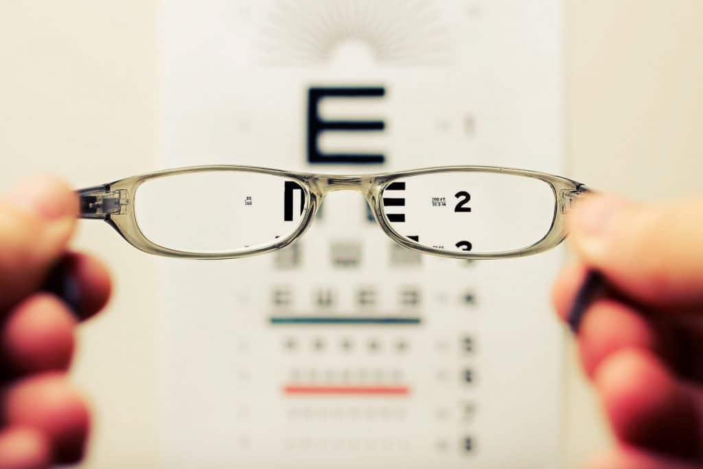 Na ilustracji zaprezentowana jest niewyraźna tablica z literami oraz okulary na pierwszym planie. Obraz widoczny przez szkła okularów jest wyraźny. Również osoby niedowidzące potrzebują ułatwień w dostępności