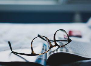 Obrazek przedstawia ujęcie na brązowe okulary położone na gazecie