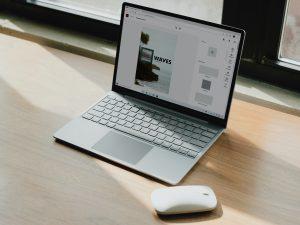 Obrazek ukazuje laptopa z myszką komputerową, które leżą na drewnianym stole